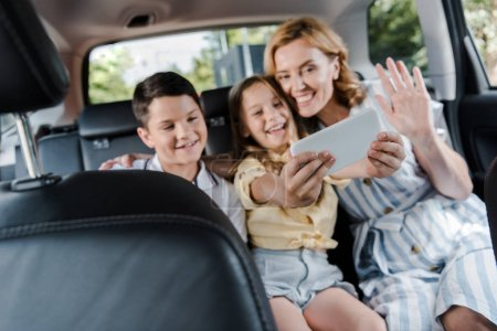 Photo for Selective focus of happy family taking selfie on smartphone in car - Royalty Free Image