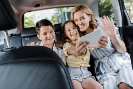 Photo pour Selective focus of happy family taking selfie on smartphone in car - image libre de droit
