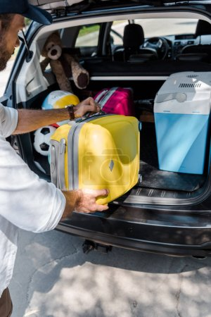 Foto de Vista recortada del hombre poniendo equipaje amarillo cerca de la bolsa de viaje rosa en el maletero del coche - Imagen libre de derechos