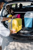 cropped view of man putting yellow luggage near pink travel bag in car trunk