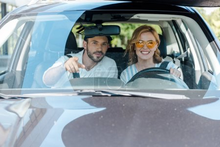 selective focus of man pointing with finger while woman driving car