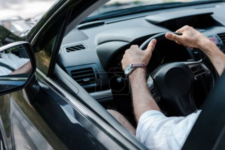 cropped view of man holding steering wheel while driving automobile