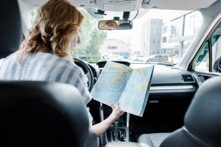 Photo pour Selective focus of happy woman holding map while sitting in car - image libre de droit