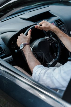 Photo for Cropped view of man holding steering wheel and driving automobile - Royalty Free Image