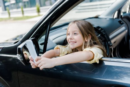 Photo for Selective focus of happy kid taking selfie on smartphone while sitting in car - Royalty Free Image