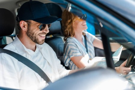Photo for Selective focus of happy man in sunglasses smiling with woman in car - Royalty Free Image