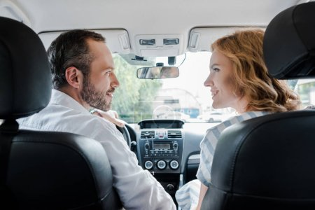 Photo for Selective focus of happy man looking at cheerful woman in car - Royalty Free Image