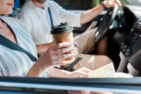 Photo for Cropped view of woman sitting in car and holding paper cup near driver - Royalty Free Image