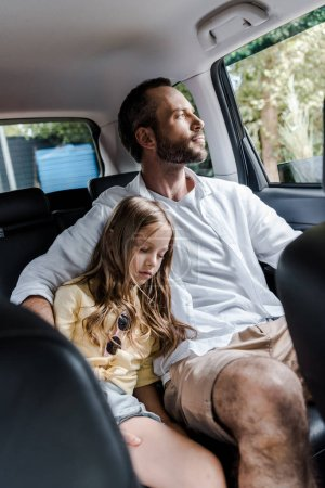 Photo pour Selective focus of bearded father sitting in car with cute daughter - image libre de droit