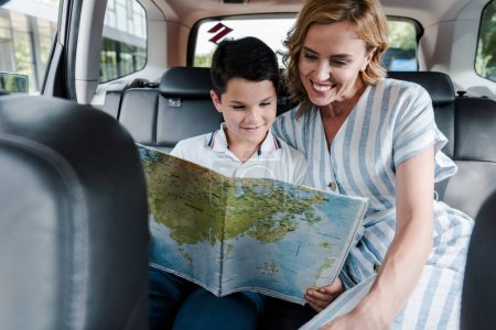Photo pour Selective focus of happy mother and son looking at map in car - image libre de droit