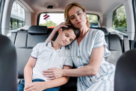 Photo pour Selective focus of mother and son with closed eyes in car - image libre de droit