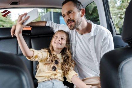 Photo pour Foyer sélectif de gosse heureux parlant selfie avec père en voiture - image libre de droit