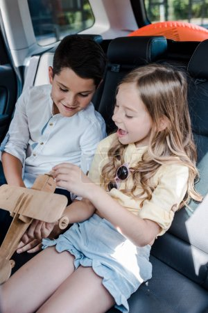 Foto de Happy sister and brother playing with wooden toy biplane in car - Imagen libre de derechos