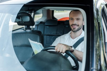 Photo pour Foyer sélectif de la voiture de conduite heureuse d'homme et de la carte de fixation - image libre de droit