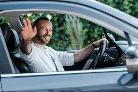 Photo for Selective focus of happy man driving car and waving hand - Royalty Free Image