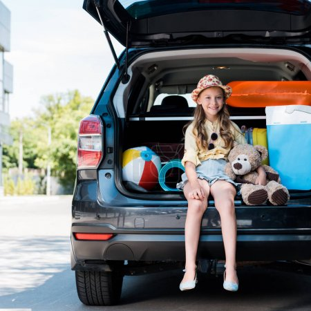 Photo for Happy kid in straw hat  holding teddy bear and sitting in car trunk near building - Royalty Free Image