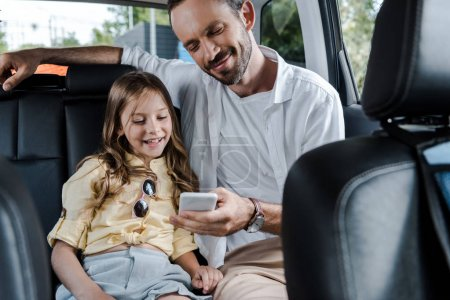 Photo pour Selective focus of happy man using smartphone near daughter in car - image libre de droit