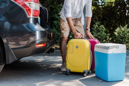 Photo pour Cropped view of man standing near luggage and car - image libre de droit