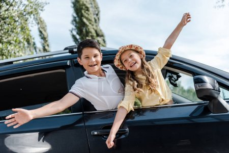 Photo for Low angle view of happy kids with outstretched hands in car windows - Royalty Free Image