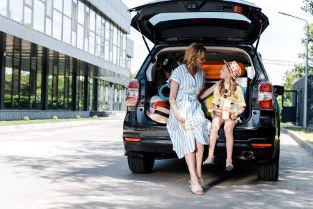 Photo pour Mère heureuse regardant fille avec biplan en bois près de la voiture - image libre de droit