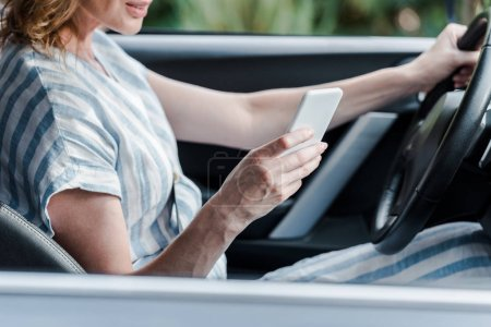 Photo for Cropped view of woman holding steering wheel and using smartphone in car - Royalty Free Image