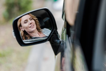 Photo for Cheerful blonde and attractive woman smiling in car window - Royalty Free Image
