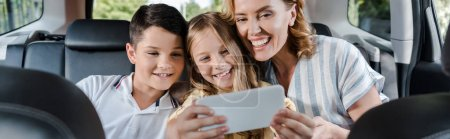 Photo pour Prise de vue panoramique de la famille joyeuse prendre selfie sur smartphone en voiture - image libre de droit