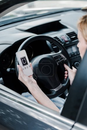 kyiv, ukraine - 26. Juni 2019: Ausgeschnittene Ansicht einer Frau mit Smartphone und uber-App auf dem Bildschirm im Auto