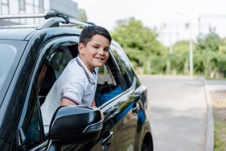 fröhlicher Junge lächelt und blickt aus dem Autofenster in die Kamera