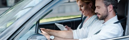 Photo for Panoramic shot of man driving car near woman using digital tablet - Royalty Free Image