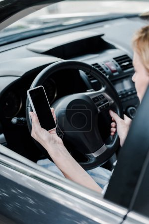 Photo for Cropped view of woman holding smartphone with blank screen in automobile - Royalty Free Image