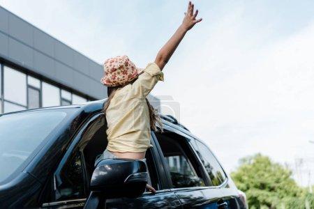 Photo pour Vue à angle bas de l'enfant avec la main tendue dans la fenêtre de la voiture - image libre de droit