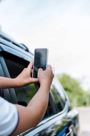Photo pour Vue recadrée de smartphone de fixation d'enfant avec l'écran blanc - image libre de droit