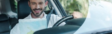 Photo for Panoramic shot of happy driver sitting in car and looking at map - Royalty Free Image