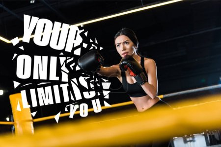Photo for Selective focus of serious woman boxing while standing in boxing gloves in gym with your only limit is you illustration - Royalty Free Image