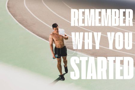 Foto de Full length view of mixed race sportsman holding towel and sport bottle at stadium with remember why you started lettering - Imagen libre de derechos