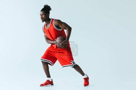 Photo pour Joueur de basket-ball américain africain dans la bille rouge de fixation de vêtements de sport sur le fond gris - image libre de droit