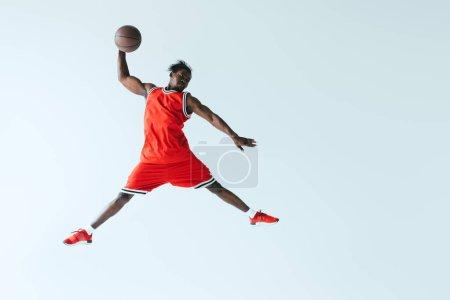 Photo pour Sportif afro-américain sautant tout en jouant au basket isolé sur gris - image libre de droit