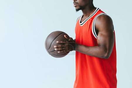 Photo pour Vue recadrée du sportif américain africain retenant la bille de basket-ball d'isolement sur le gris - image libre de droit