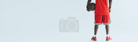 Photo for Cropped view of african american basketball player holding ball on grey background, panoramic shot - Royalty Free Image