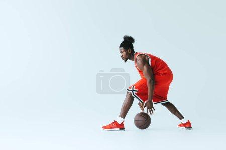 Photo pour Sportif sportif africain sportif américain jouant au basket-ball sur le fond gris - image libre de droit