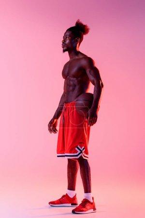 Photo pour Beau joueur de basket-ball américain africain regardant loin sur le fond rose et pourpre de gradient avec l'éclairage - image libre de droit