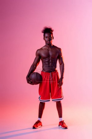 Photo for Shirtless african american basketball player looking at camera on pink and purple gradient background with lighting - Royalty Free Image