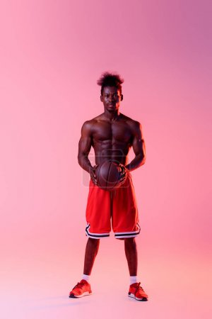 Photo for Confident african american basketball player with muscular torso looking at camera on pink and purple gradient background with lighting - Royalty Free Image