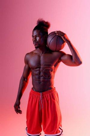 Photo pour Confiant, torse nu africain sportif américain regardant loin tout en tenant la balle sur le fond rose avec le gradient - image libre de droit