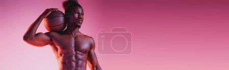 Photo pour Tir panoramique de joueur de basket-ball américain africain retenant la bille et regardant loin sur le fond rose et pourpre de gradient - image libre de droit