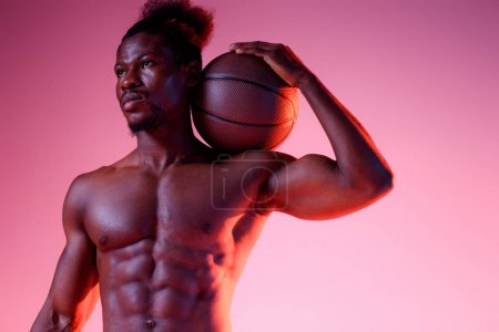 Photo for Serious african american sportsman with muscular torso holding ball and looking away on pink and purple gradient background - Royalty Free Image
