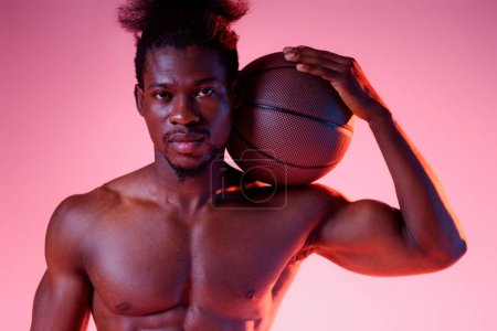 confident, shirtless african american basketball player holding ball and looking at camera on pink background with gradient