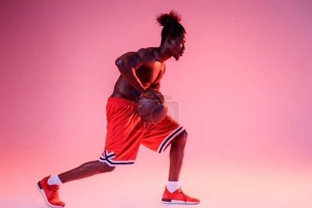 Foto de Deportista afroamericano en rojo corto jugando baloncesto en el fondo degradado rosa y púrpura - Imagen libre de derechos