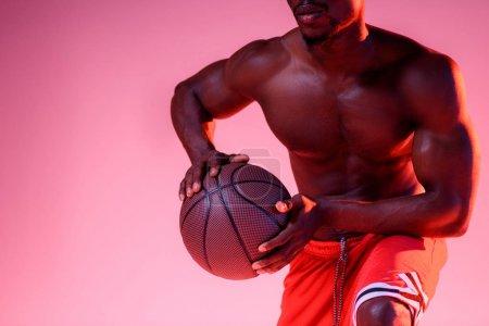 Photo pour Vue recadrée du sportif américain africain torse nu jouant au basket-ball sur le fond rose avec le gradient - image libre de droit
